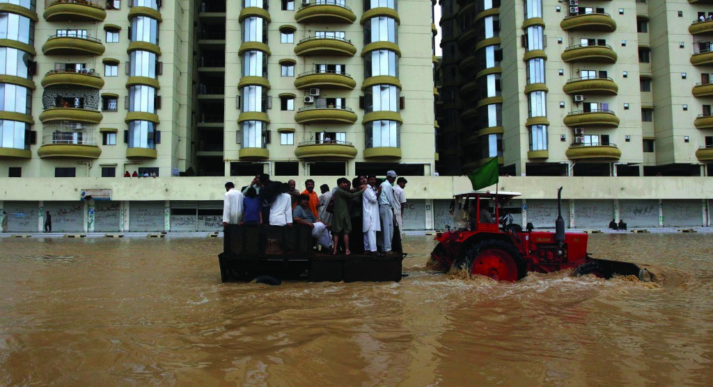 A tractor tows residents through flood waters to a safe place on the outskirts of Karachi. Heavy rains that caused flash floods and collapsed houses in different parts of Pakistan have killed 53 people over the past three days, a Pakistani official said Monday. (REUTERS/Akhtar Soomro)