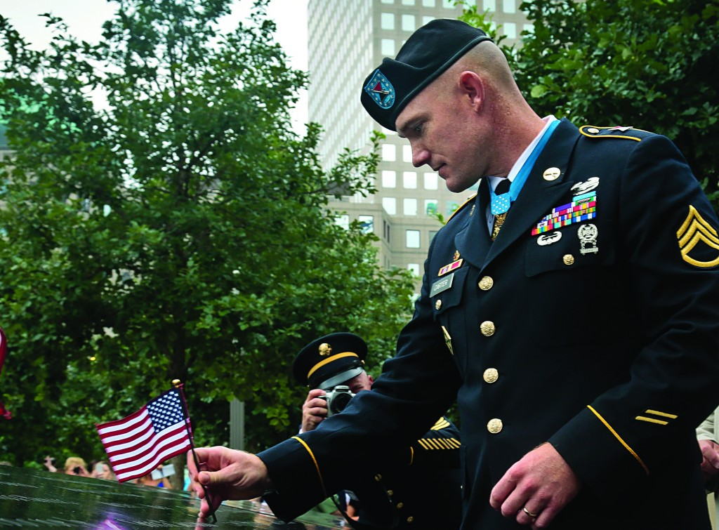 Medal of Honor recipient Staff Sgt. Ty Carter places a flag on a section of the 9/11 Memorial on Thursday, in New York. The section carried the names of Pentagon victims of the World Trade Center attacks. Carter, one of only five living recipients of the medal who fought in post-9/11 conflicts, was cited for his actions during a battle in Afghanistan.(AP Photo/Bebeto Matthews)
