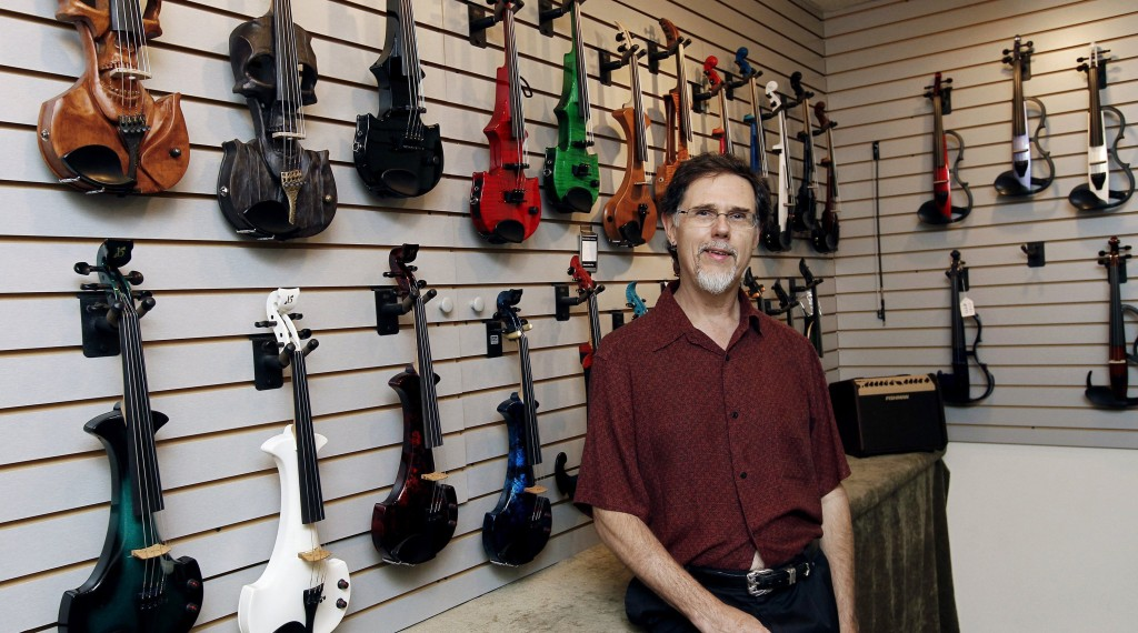 Blaise Kielar poses for portrait with the wide selection of electric violins at the Electric Violin Shop near the RTP inDurham, North Carolina Thursday. The company  sells many items over the Internet. (Chris Seward/Raleigh News & Observer/MCT)