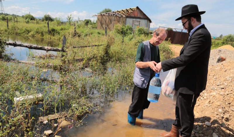 Rabbi Yaakov Santikov assisting a local resident.