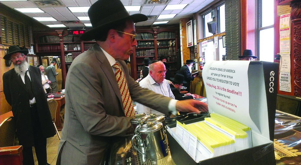 Moshe Metzger, the longtime gabbai of the Shomrei Shabbos shul in Boro Park, stands near an Agudath Israel voter registration station. Friday is the deadline to register to vote in city elections in November. (Agudath Israel of America)