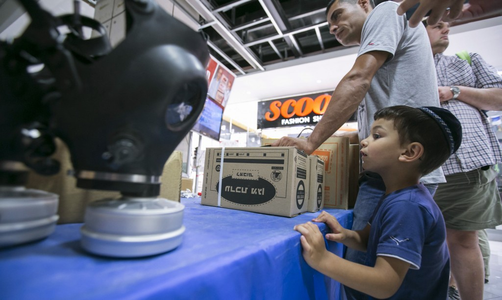 An Israeli child looks on as a man collects gas masks at a distribution point at a shopping mall in Yerushalayim on Monday. Thousands of Israelis lined up for gas masks at nationwide distribution centers or phoned in orders, fearing a deadly chemical weapons attack in Syria may wind up ensnaring their own nation in conflict, officials and analysts said on Monday. (REUTERS/Baz Ratner)