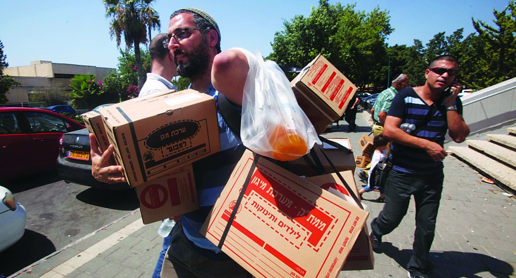 Israelis carry boxes with gas masks at a distribution center in Tel Aviv on August 28, 2013. As talks of an international attack on Syria heightened, the demand for gas masks in Israel rose. (Roni Schutzer/Flash90)