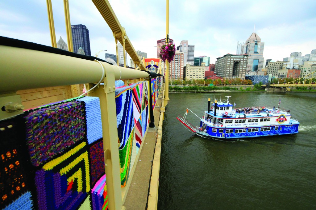 A riverboat passes under a Pittsburgh bridge on Sunday, Aug. 11, 2013 after more than 1,800 knitters covered the bridge in 3,000 feet of colorful yarn. Volunteers worked all weekend to attach 580 blanket-sized, hand- knitted panels to the pedestrian walkways. Organizers say it is the nation's largest yarn bomb ever. (AP Photo/Gene J. Puskar)