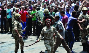 Egyptian security forces try to keep angry crowds away from the al-Fatah mosque, where supporters of the Muslim Brotherhood have barricaded themselves, in Ramses Square in downtown Cairo, Egypt, Saturday. (AP Photo/Hussein Tallal)
