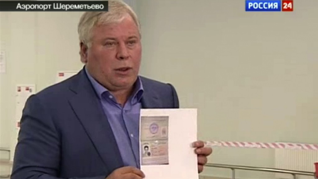 Russian lawyer Anatoly Kucherena shows a temporary document to allow Edward Snowden to cross the border into Russia while speaking to the media after visiting National Security Agency leaker Edward Snowden at Sheremetyevo airport outside Moscow, Russia. Snowden was granted asylum in Russia for one year and left the transit zone of Moscow's airport, his lawyer said. (AP Photo/Russia24 via APTN)