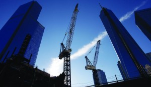 Construction cranes work between Four World Trade Center, left, and One World Trade Center, right, Sunday, in New York. Twelve years after terrorists destroyed the old World Trade Center, the new World Trade Center is becoming a reality, with a museum commemorating the attacks and two office towers where thousands of people will work, set to open within the next year. (AP Photo/Mark Lennihan)