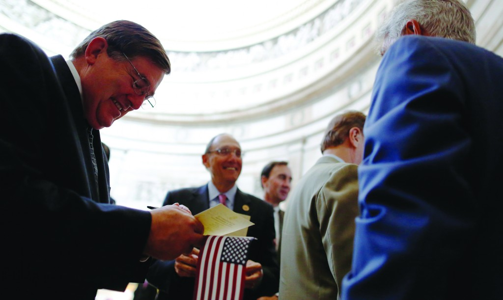 U.S. Representative Michael Burgess (R-TX) (L) autographs another congressman's program leaflet as members of Congress gather in the rotunda before observing a moment of silence Wednesday at the Capitol in Washington. (REUTERS/Jonathan Ernst)