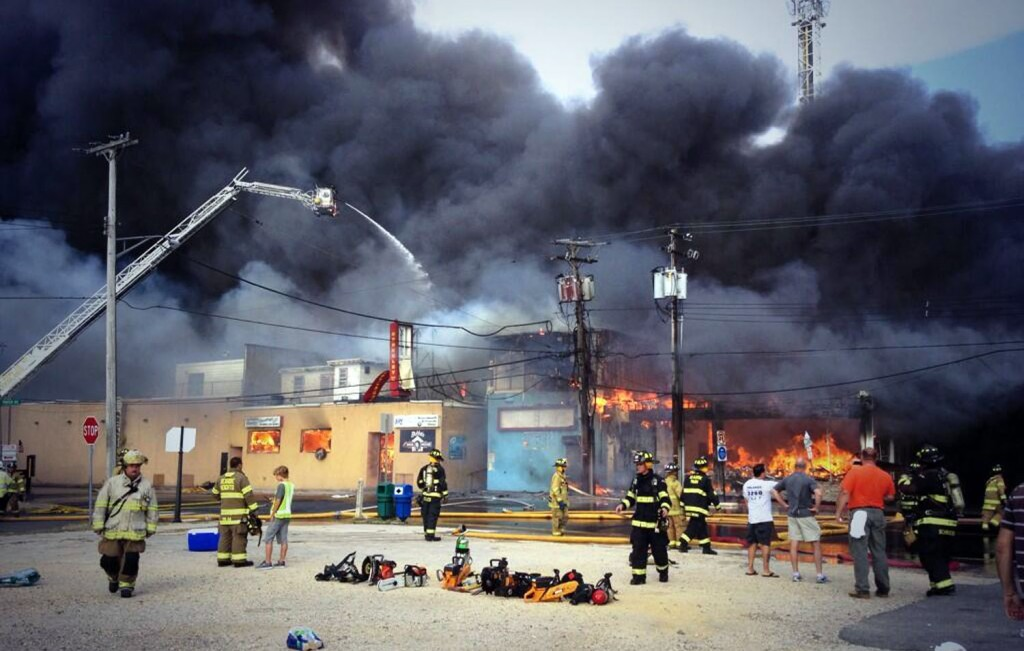 Firefighters battle a raging fire on the boardwalk in Seaside Heights, N.J. that apparently started in an ice cream shop and has spread several blocks down, Thursday, Sept. 12, 2013. The boardwalk was damaged in Superstorm Sandy and was being repaired. (AP Photo/The Asbury Park Press, Kristi Funderburk)