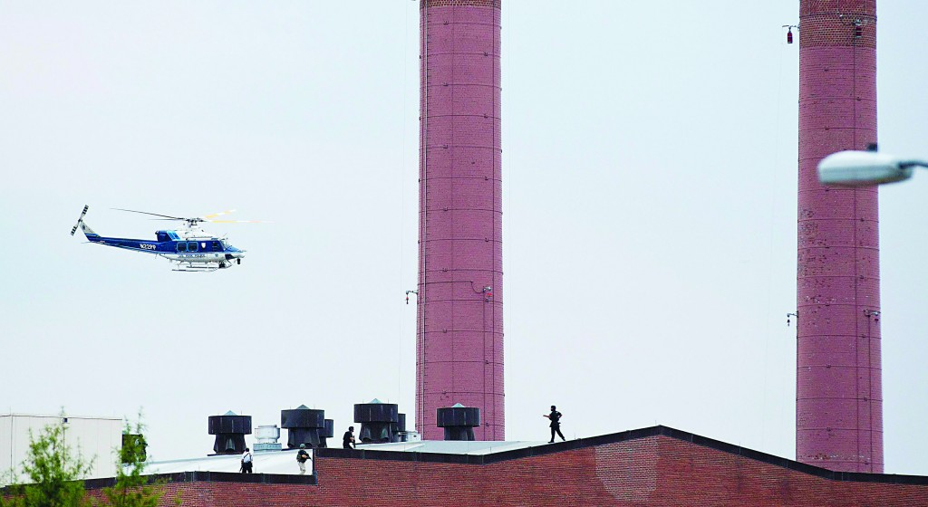 A police helicopter flies overhead as police walk on the roof of a building as they respond to the shootings at the Washington Navy Yard in Washington, D.C. (REUTERS/Joshua Roberts)