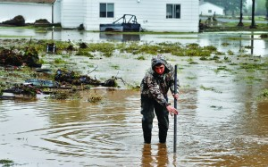 Local man Joey Schendel, 19, looks for submerged items while helping neighbors salvage and clean their property in an area inundated after days of flooding, in Hygeine, Colo., Monday. (AP Photo/Brennan Linsley)