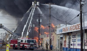 Firefighters battle a fire on the Seaside Heights, N.J. boardwalk Thursday, Sept. 12, 2013. The fire started in the vicinity of an ice cream shop and burned several blocks of boardwalk and businesses in a town that was still rebuilding from damage caused by Superstorm Sandy. (AP Photo/The Asbury Park Press, Bob Bielk)