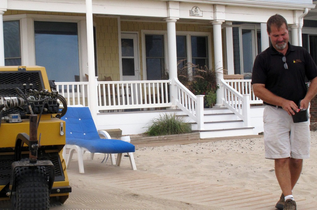 Marty Sudol pilots a remote-controlled mechanical beach rake that strains debris from sand in front of a home on the Manasquan, N.J. beachfront. He says his company was so busy cleaning sand this summer that he didn't get to relax on the beach once. (AP Photo/Wayne Parry)