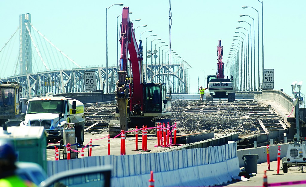 In a photo provided by the Bay Area Toll Authority, workers demolish a portion of the San Francisco-Oakland Bay Bridge on Thursday, Aug. 29. in Oakland, Calif. Workers must remove the section to allow the bridge's newly-built eastern span to open by Tuesday morning. (AP Photo/Noah Berger, Bay Area Toll Authority)