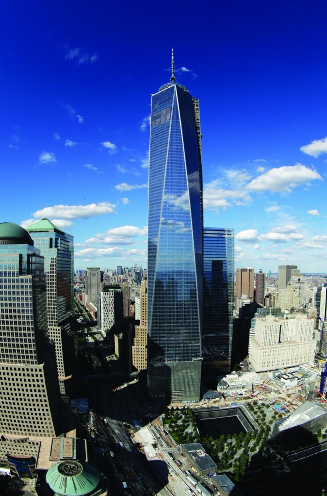 In this photo taken with a fisheye lens, One World Trade Center (C) overlooks the wedge-shaped pavilion entrance of the National September 11 Museum, (lower R) and the square outlines of the memorial waterfalls in New York. (AP Photo/Mark Lennihan)