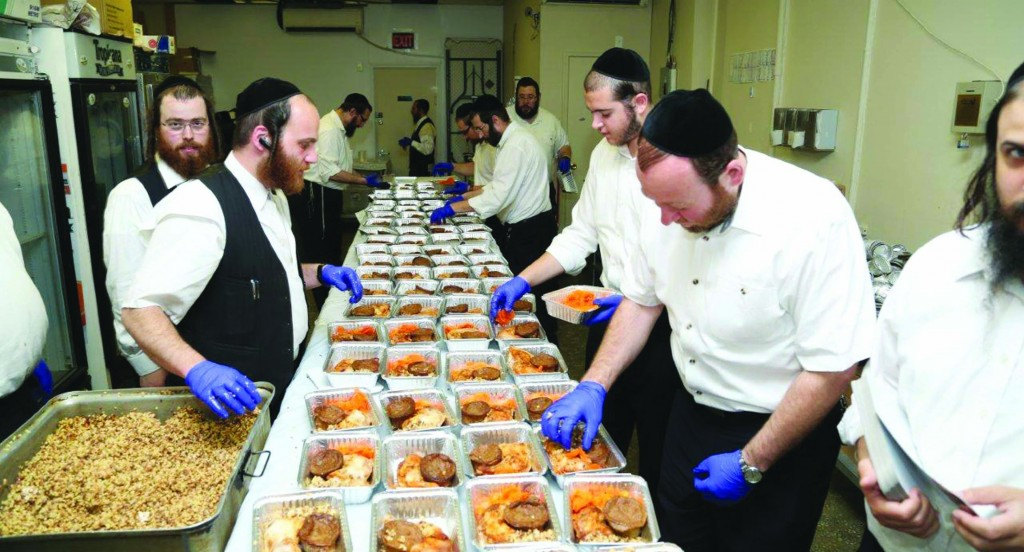 Volunteers of Bikur Cholim Yad Ephraim prepare hundreds of food packages for people spending Rosh Hashanah in the hospital. (Heshy Rubinstein/Dee Voch)