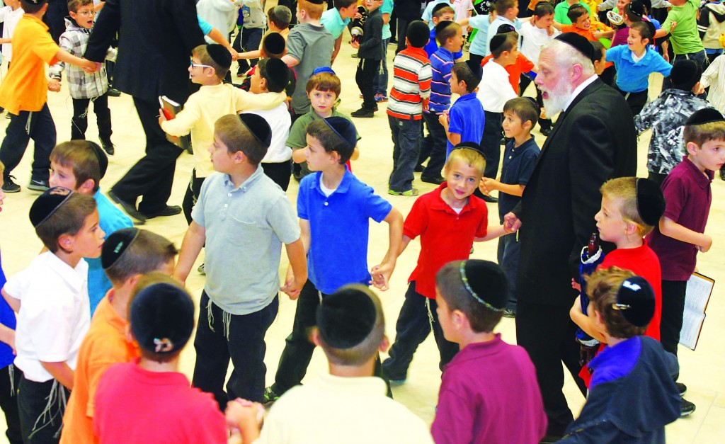 Rav Shmuel Strickman, menahel of Yeshiva Darchei Torah's lower elementary school, dances with talmidim Monday to introduce the basics of the Hakafos to grades 1 and 2. Many of the children brought their own mini-sifrei Torah, while others held Chumashim. Rebbeim said the introductory pesukim, and then they all broke out into joyous dancing accompanied by music.