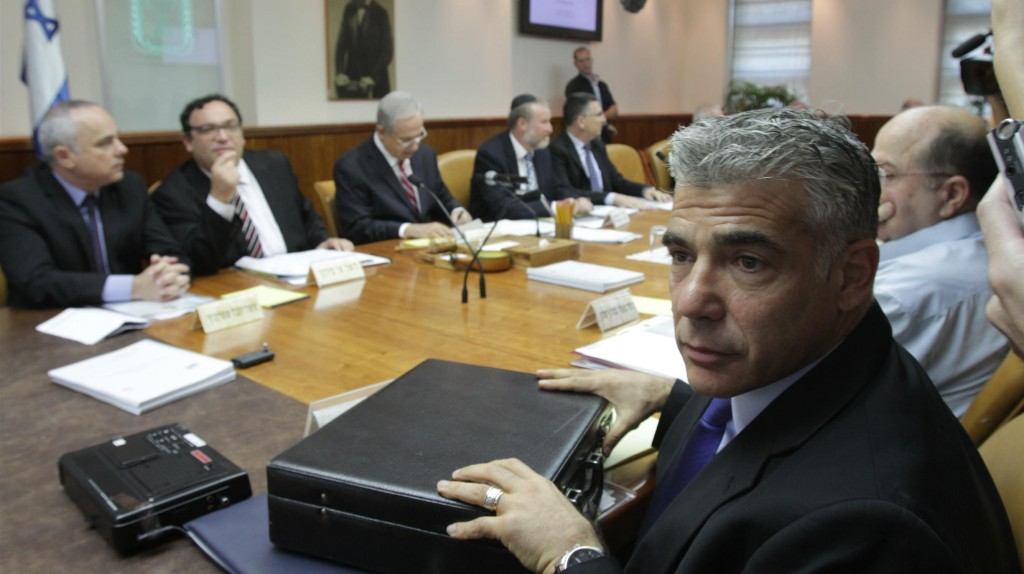 Finance Minister Yair Lapid seen with his briefcase at the weekly cabinet meeting. (Alex Kolomoisky/POOL/FLASH90)