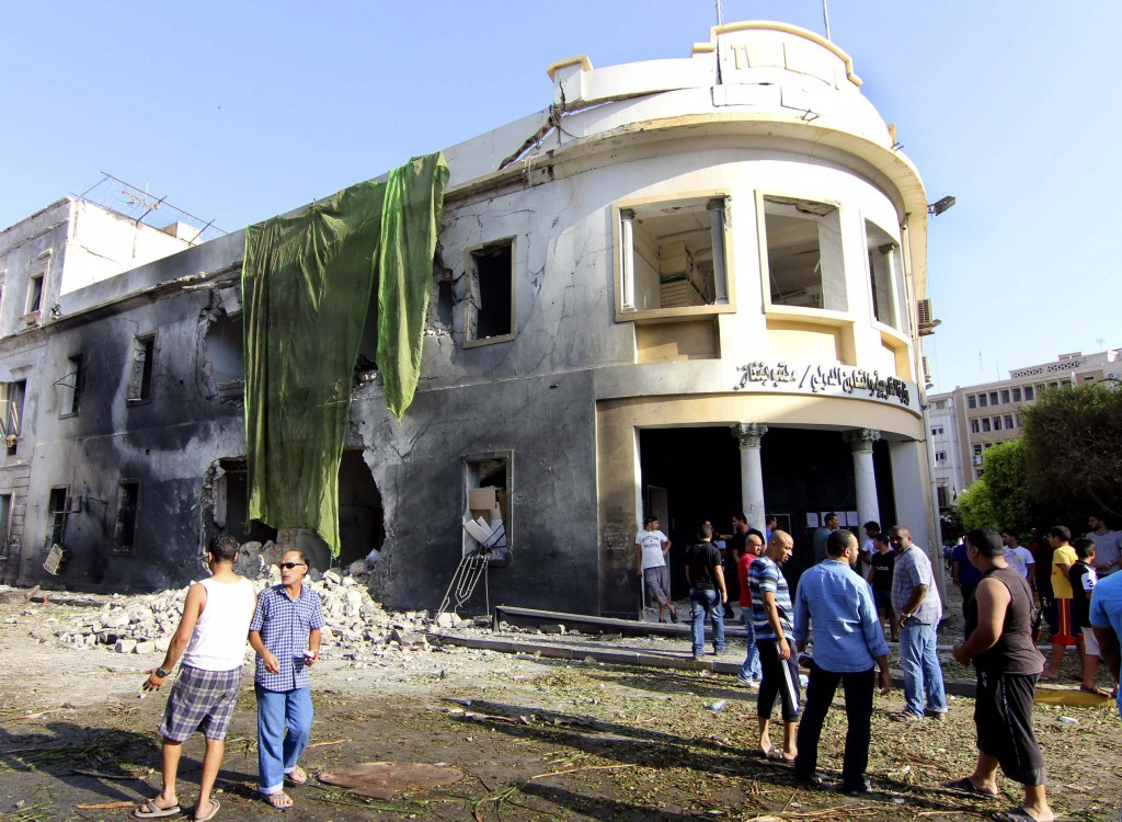 People gather to look at the site of a car bombing in Benghazi, Libya, Wednesday. (AP Photo/Mohammed el-Shaiky)