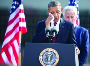 President Barack Obama, accompanied by Defense Secretary Chuck Hagel, wipes his face as he speaks during a 9/11 remembrance ceremony at the Pentagon, Wednesday (AP Photo/Manuel Balce Ceneta)