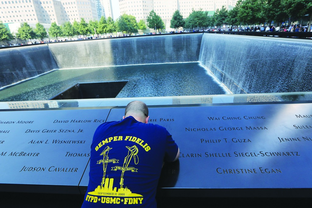 Dennis Palmer, of Bay Shore, N.Y., pays his respects to family and friends at the South Pool of the 9/11 Memorial during the 12th anniversary of the attacks. (AP Photo/Mary Altaffer, Pool)