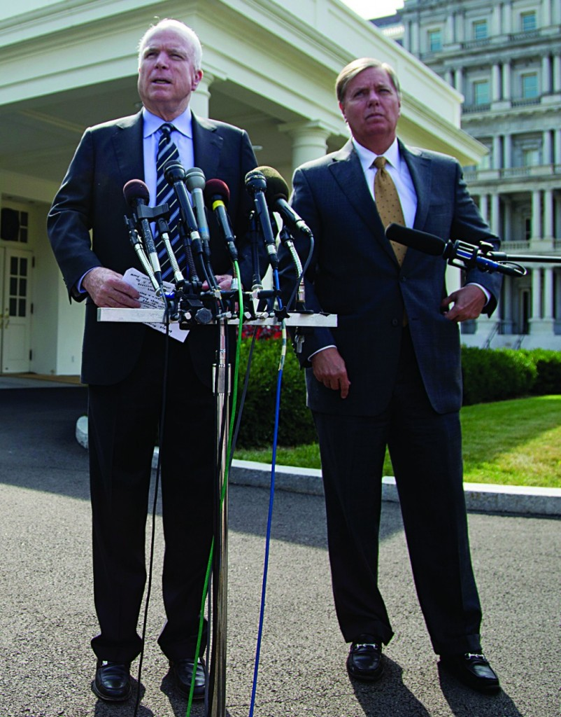 Sen. John McCain (R-Ariz.)(L), accompanied by Sen. Lindsey Graham (R-S.C.) speaks with reporters outside the White House in Washington, Monday, following a closed-door meeting with President Obama to discuss the situation in Syria. (AP Photo/Evan Vucci)