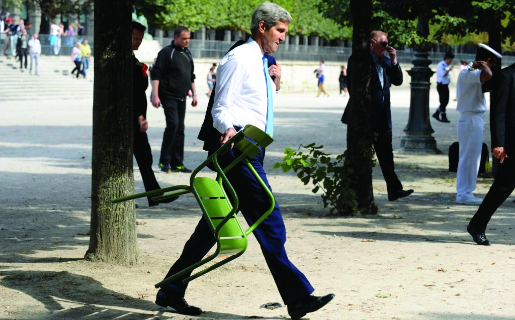 Secretary of State John Kerry carries a chair at Les Tuilleries park in Paris Sunday, before settling into a conversation with other U.S. representatives. (REUTERS/Susan Walsh/ Pool)