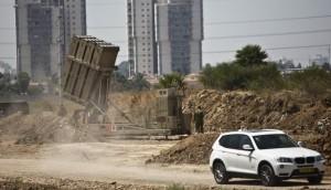 A car drives by as an Israeli soldier walks near an Iron Dome rocket interceptor battery deployed near Tel Aviv.  (REUTERS/Nir Elias)