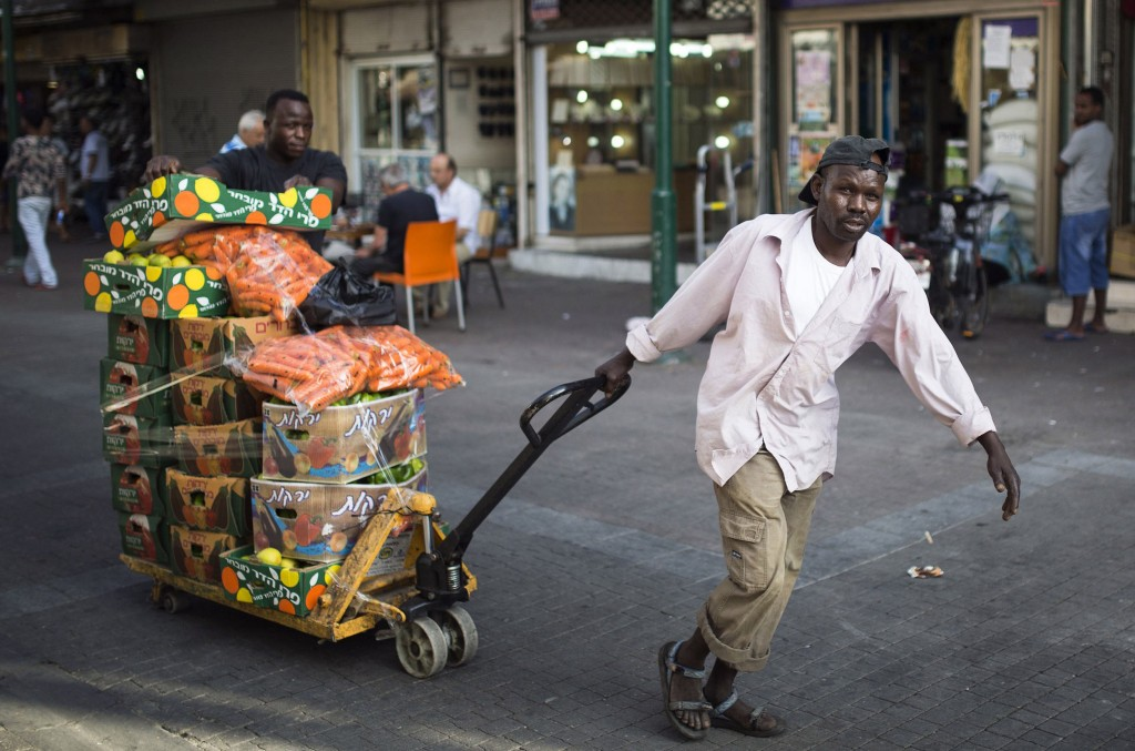 An African migrant pulling a cart loaded with vegetables in south Tel Aviv. (REUTERS/Amir Cohen)