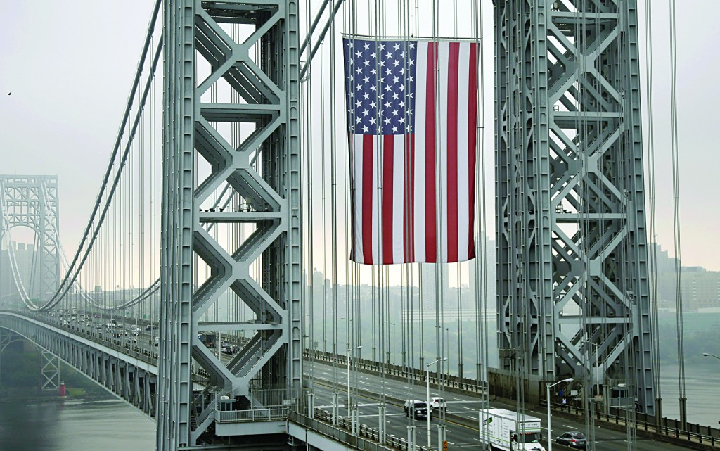The largest free-flying American flag in the world flies over the George Washington Bridge, in Fort Lee, N.J. The Port Authority of New York and New Jersey says the flag flew on Labor Day under the arch of the New Jersey tower. The flag — 90 feet by 60 feet, with 5-foot wide stripes and 4-foot diameter stars — is meant to honor working men and women across the country. (AP Photo/Mel Evans)