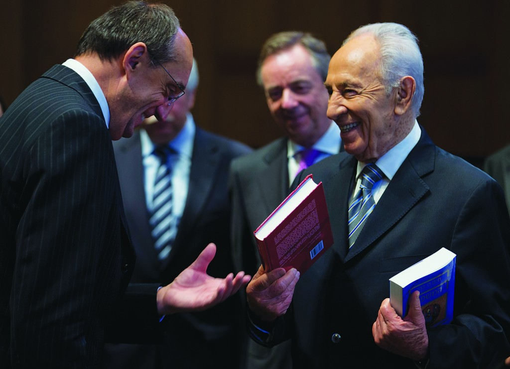 Israel's President Shimon Peres (second right) offers books to International Court of Justice president Judge Peter Tomka of Slovakia (L) in The Hague, Netherlands, on Monday. The court, also known as Peace Palace, is the principal judicial organ of the United Nations. (AP Photo/Peter Dejong)