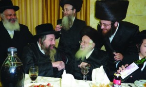 "(L-R) Rachmastrivka Rebbe of Yerushalayim, shlita, lhb""c Harav Nuta Freund, zt""l, and grandson Rabbi Tuvia Freund (leaning over his grandfather) at the bar mitzvah of a grandson."