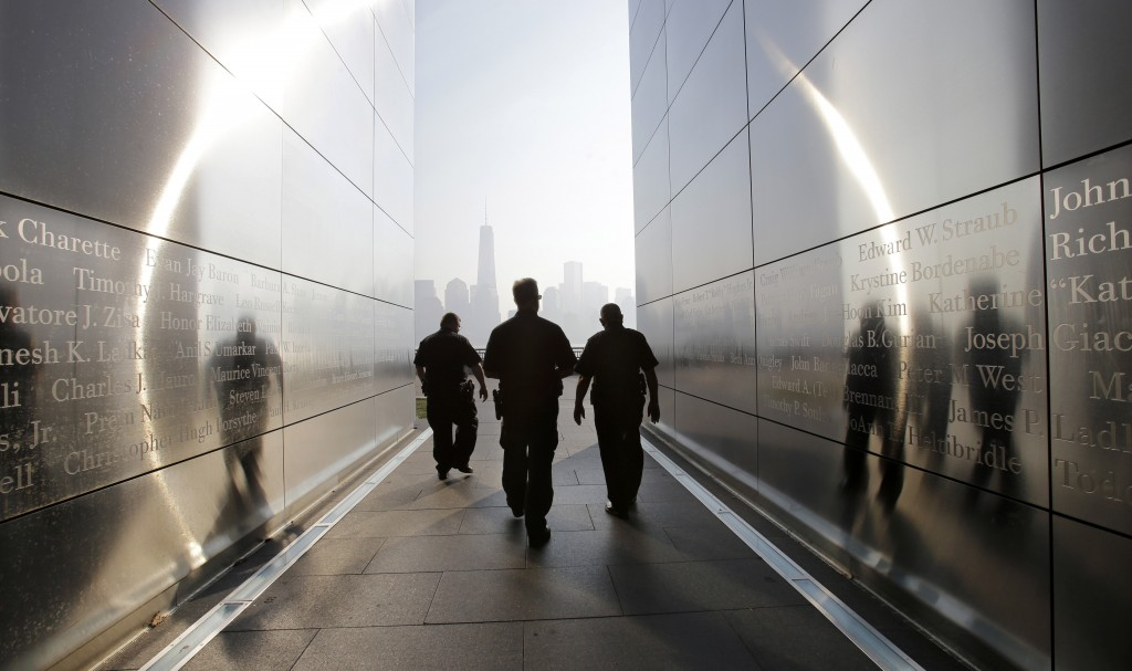 """Three police officers walk through the """"Empty Sky"""" memorial to New Jersey's victims of the Sept. 11, 2001 terrorist attacks on Wednesday, Sept. 11, 2013, in Jersey City, N.J. (AP Photo/Mel Evans)"""