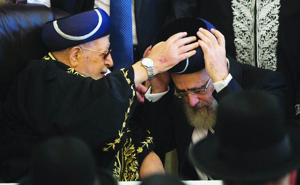 Hagaon Harav Ovadia Yosef, shlita, puts the traditional cap on the head of his son, the new Rishon LeTzion, Harav Yitzchak Yosef, shlita, during a ceremony at the Rabban Yohanan Ben Zakai Synagogue in Yerushalayim on Monday. (Yonatan Sindel/Flash90)