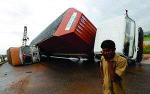 A man stands next to overturned trucks on a highway after Cyclone Phailin hit Girisola town in Ganjam district in the eastern Indian state of Orissa. (REUTERS/Adnan Abidi)