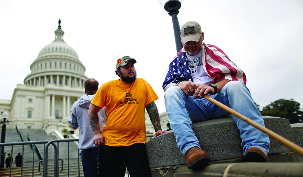 U.S. Army veterans Peter Marshall Bland (C) and James Taylor (R) of Fort Hood, Texas, end a day of protest with a group from the Million Vet March on the Memorials, rallying against the closure of the U.S. National World War II Memorial due to the current U.S. government shutdown, in front of the U.S. Capitol in Washington, Sunday. (REUTERS/Jonathan Ernst)