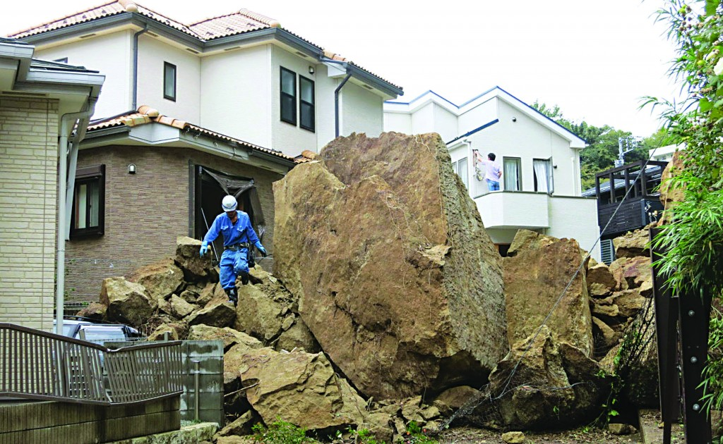 A firefighter walks over rocks fallen from a cliff over a garage and a road in a residential area in Kamakura, southwest of Tokyo, after a powerful typhoon hit Japan's metropolitan area Wednesday. (AP Photo/Kyodo News)