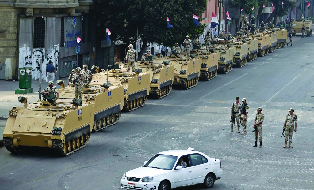 In this August 16 file photo, Egyptian army soldiers take their positions on top of and next to their armored vehicles to guard an entrance of Tahrir Square, in Cairo. (AP Photo/Hassan Ammar, File)
