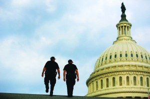 U.S. Capitol Police return to patrol after a brief meeting to discuss how to handle tourists turned away from the shuttered visitor's center at the U.S. Capitol in Washington, October 1, 2013. The U.S. government began a partial shutdown for the first time in 17 years, potentially putting as many as one million workers on unpaid leave, closing national parks and stalling medical research projects. See pages D1, D3-4. (REUTERS/Jonathan Ernst)