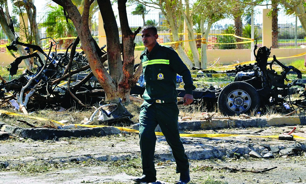 An Egyptian emergency responder walks through the site of a suicide car bombing on a security headquarters in the southern Sinai town of el-Tor, Egypt, Monday. (AP Photo/Mostafa Darwish)