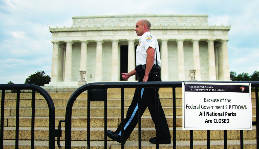 "A U.S. Park Police officer walks behind a barricade with sign reading ""Because of the Federal Government SHUTDOWN, All National Parks are Closed"" in front of the Lincoln Memorial in Washington, D.C., Tuesday. (AP Photo/Carolyn Kaster)"