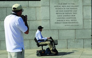 Jeff Morgan, left, takes a photograph of his father, World War II Marine veteran Eugene Morgan, both of Collierville, Tenn., as they visit the World War II Memorial in Washington, Wednesday. (AP Photo/Susan Walsh)