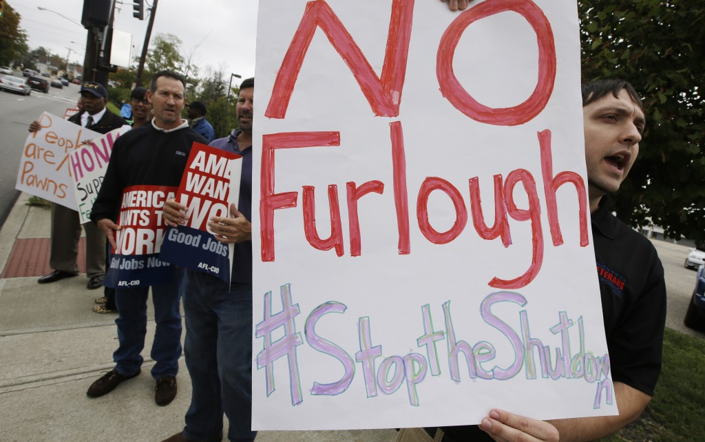 Federal workers protest outside the Department of Health and Human Services CDC offices, Tuesday, Oct. 15, 2013, in Cincinnati, Ohio. The government shutdown is entering its third week. (AP Photo/Al Behrman)