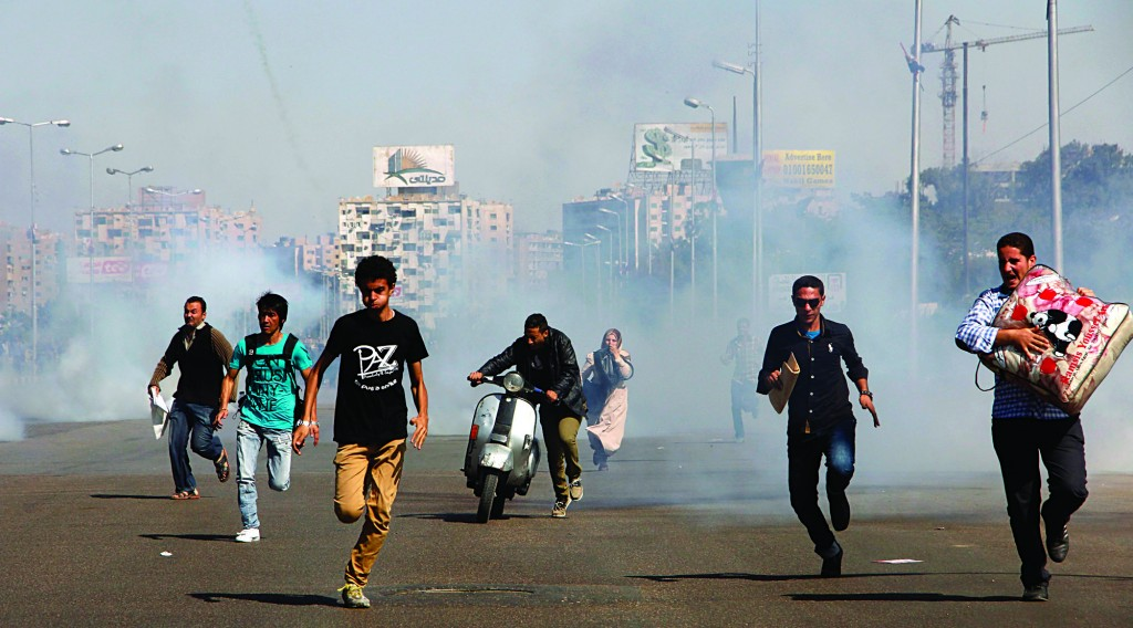 Egyptians run from tear gas after clashes erupted between Al-Azhar students and police forces during a protest in the Nasr City district of Cairo, Sunday. (AP Photo/Heba el-Kholy, El Shorouk Newspaper)