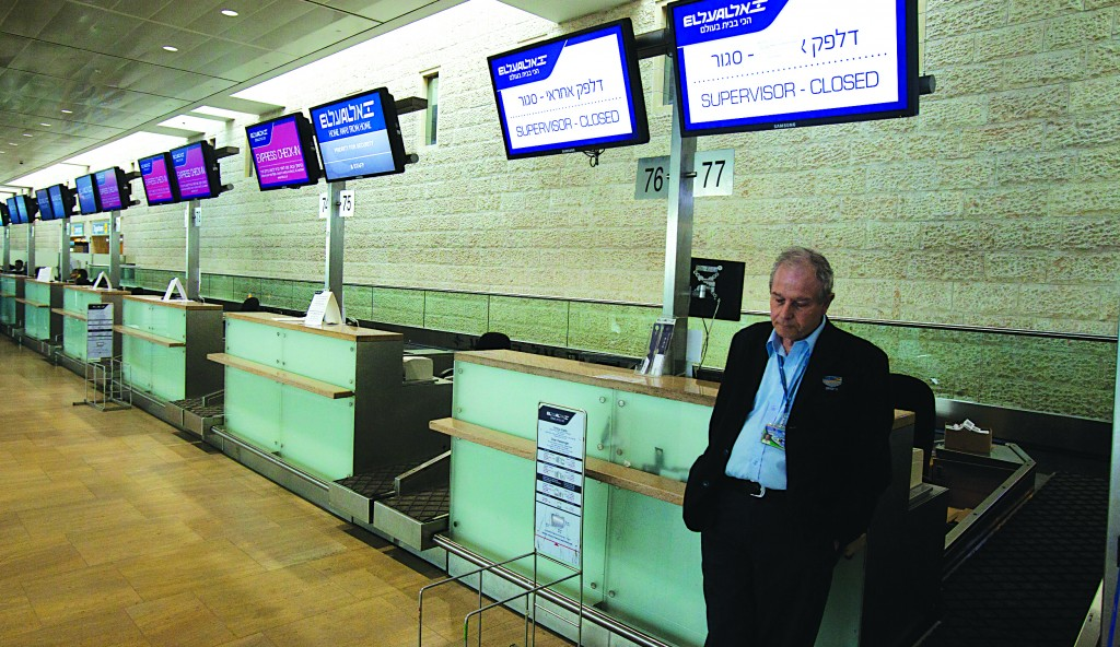 An Israeli traveler waits next to deserted El Al check-in counters at Ben-Gurion International Airport during an airline workers strike in April. Labor disputes are blamed for much of the airline's financial difficulty. (Flash90)