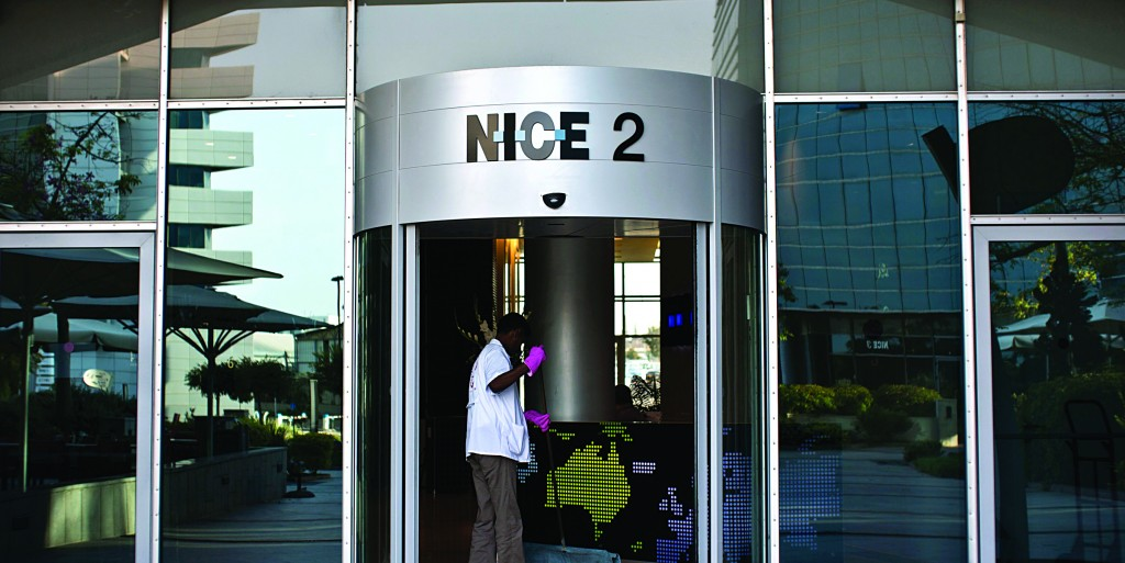 A worker cleans under the logo of Nice Systems at the entrance of its headquarters in the city of Raanana, north of Tel Aviv. (REUTERS/Nir Elias)