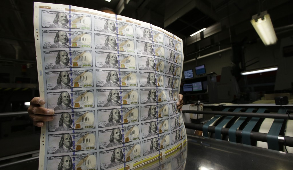 This Sept. 24, 2013 file photo shows sheets of uncut $100 bills moved during the printing process at the Bureau of Engraving and Printing Western Currency Facility in Fort Worth, Texas. (AP Photo/LM Otero, File)