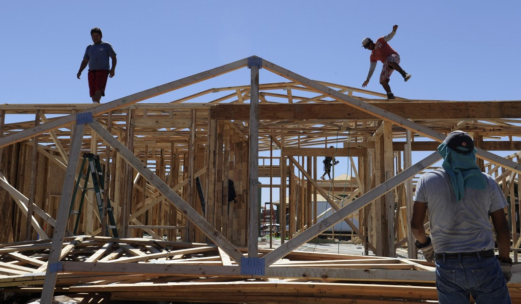 A man steadies himself as he and others work on framing new houses, in Odessa, Texas. Hundreds of houses are being built in the West Texas oil town to accommodate the influx of people working in the oil fields. (AP Photo/Pat Sullivan)