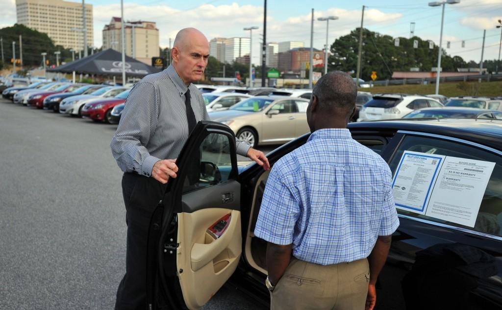 Lexus salesman Randy Autrey, left, shows Raymone Sleurancois a car at a dealership in Smyrna, Georgia, on October 1, 2013. (Brant Sanderlin/Atlanta Journal-Constitution/MCT)