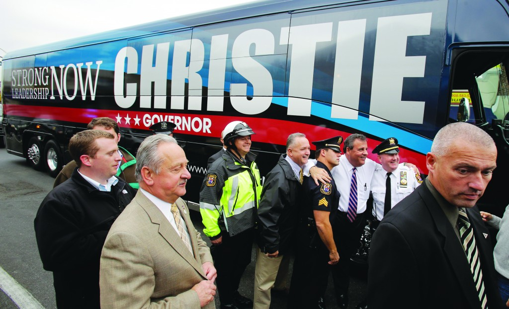 Gov. Chris Christie, third right, poses beside his campaign bus with police officers in Linden, N.J., Wednesday. (AP Photo/Mel Evans)
